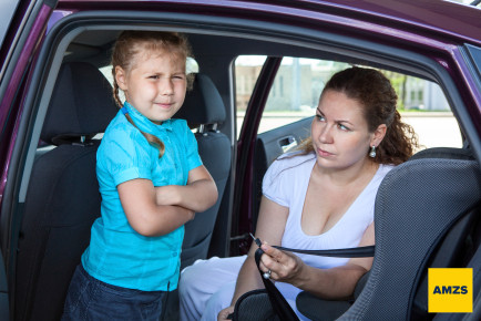 Mother trying to ask a girl get in child safety seat against the wishes
